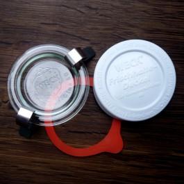 Jedes der Weck-Gläser wird mit dem Glasdeckel, einem Gummiring und 2 Metallklammern verschlossen. Als Zusatz sind weiße Frischhaltedeckel erhältlich.